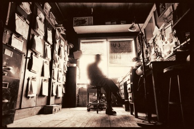 A man sits silhuetted in the office of his automotive parts store after it has closed.